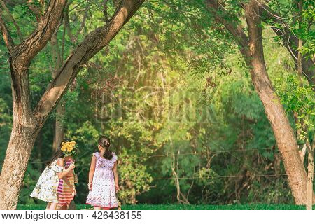 Asian Girls And Friends Playing Together On Lawn Through Green Garden. Happiness Girl Friends Having