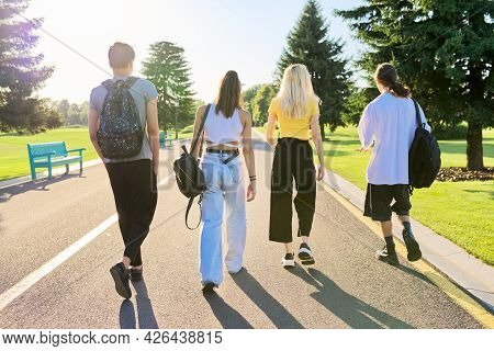 Group Of Teenage Friends On Sunny Summer Day Walking Together On Road, Back View