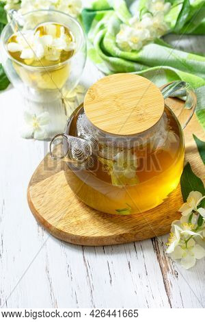 Therapeutic Herbal Tea. Hot Jasmine Tea With Jasmine Flowers In A Glass Teapot On A Rustic Wooden Ta