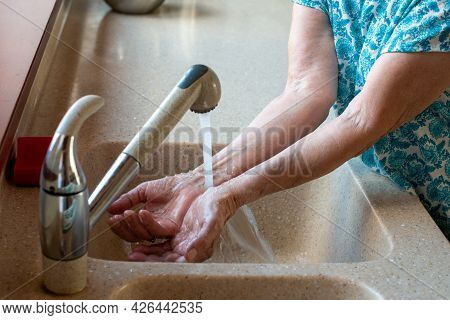 Senior Womans Hands Under Cold Running Water.  Close Up. How To Stay Cool In Hot Weather. Beat The H