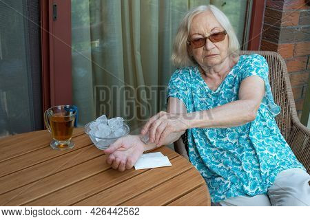 Senior Woman Holds Ice Cube On Her Wrist. How To Stay Cool In Hot Weather. Beat The Heat.