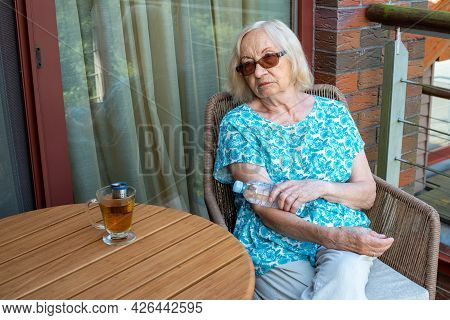 Senior Woman Holds Bottle With Cold Water On Her Elbow Bend. How To Stay Cool In Hot Weather. Beat T