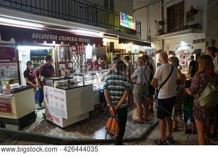 Peschici - 29/06/2021: Famous Italian Ice Cream Shop With People In Peschici At Night , Puglia, Ital