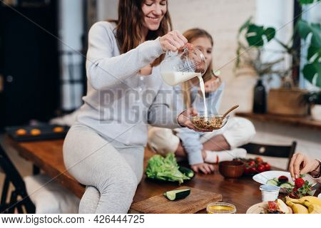 Young Woman Sits On The Kitchen Table And Pours Milk Into Muesli.