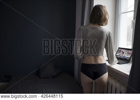 A Girl In A Silver Top And Shorts Looks At The Screen Of The Computer At The Window.