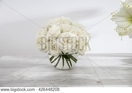 White Roses, Lily In Round Vases On The Table For A Special Occasion As A Kitchen Decoration. Copy S