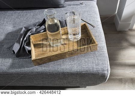 A Refreshing Glass Of Water, A Bottle Of Water And On A Tray, A Linen Napkin On The Couch In The Sum