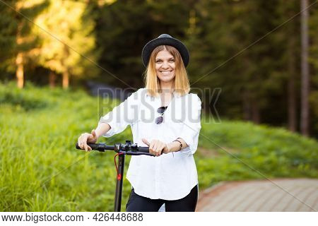 Trendy Carefree Woman In White Shirt And Black Hat Ride On Kick Scooter Outdoor In Summer Park Stree