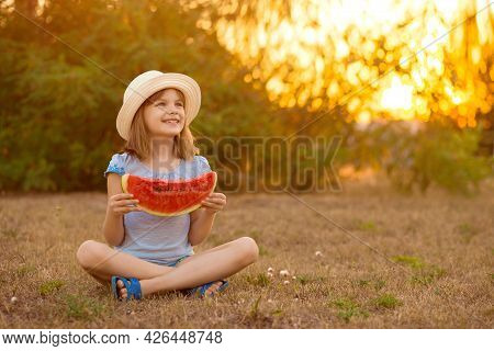 Adorable Baby Girl In Straw Hat Sit With Cross Legs On Green Grass, And Eagerly Eats Juicy Watermelo