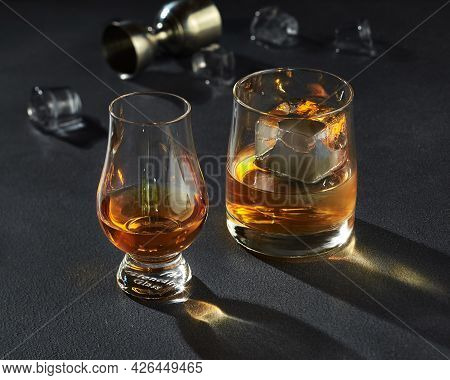 Two Glasses Of Amber Whiskey With Ice On Dark Background