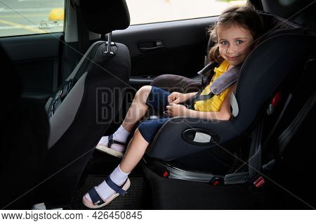 Cute Baby Girl Belted In A Safety Child Car Seat, Smiles While Looking At The Camera. Using A Child