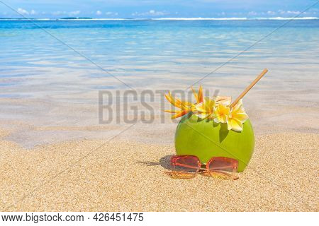 Fresh Coconut Juice With Sunglasses On The Background Of A Beautiful Beach.