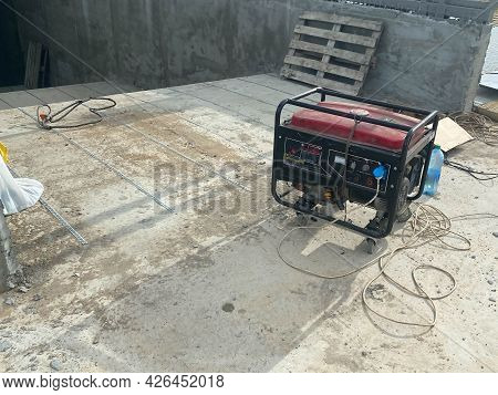 Large Industrial Red Electric Generator Running On Gasoline Or Kerosene At A Construction Site