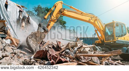 Demolition Of Building. Excavator Breaks Old House. Freeing Up Space For Construction Of New Buildin