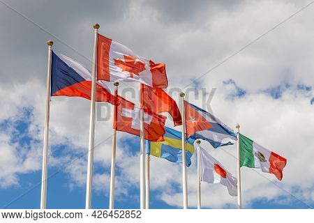 Flags On Flagpoles, Against A Cloudy Sky. Flags Of Various Countries Of The World Flutter In The Win