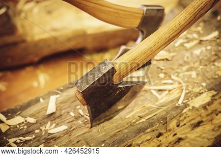 Carpentry Concept. The Axes Are Driven Into A Wooden Log. Works In A Carpentry Workshop