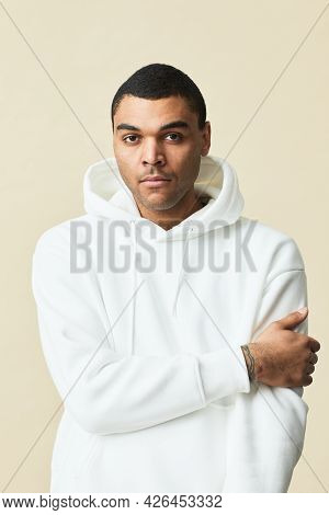 Minimal Waist Up Portrait Of Handsome Mixed-race Man Wearing White Hoodie And Looking At Camera Whil