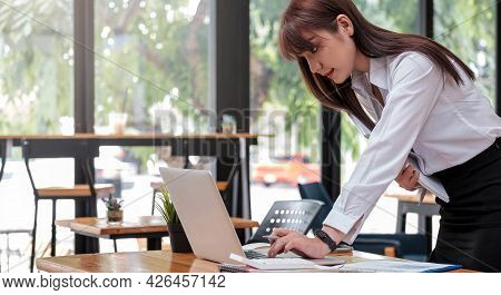 Smart Businesswoman Analyzing Business Data, Reviewing Profits Report And Working On Laptop Computer