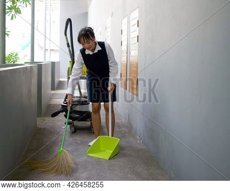 Young Hotel Maid Cleaning Floor With Broom And Dustpan. Housekeeping Cart On The Corridor In Front O