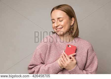 Happy Pleased Woman Hug Smartphone. Young Blond Female Press Mobile Phone To Chest Get Pleasant Mess