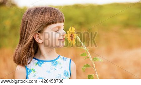 Adorable Little Girl With Fluttering Hair And Smell Sunflower Flower, Walking Outdoor In Summer Holi