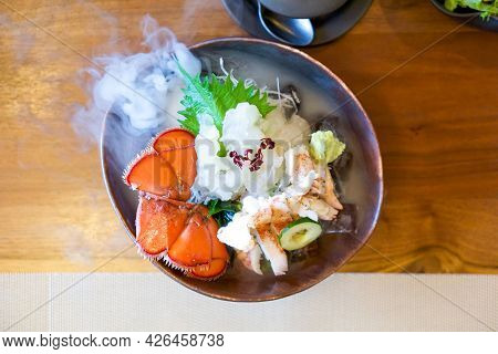 Live Canadian Lobster Sashimi On Brown Ceramic Plate With A Smoke Of Dry Ice. Served Two Ways Fresh