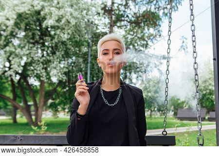 Young Stylish Business Woman With Short Hair And Nose Piercing Sitting On The Swing And Smoking Elec