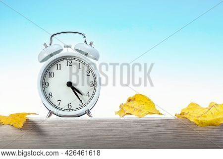 Autumn Season Time With Alarm Clock And Dry Gold Leaves On Blue Sky Background.