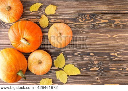 Autumn Harvest.  Pumpkins With Autumn Leaves On Wooden Background With Copy Space. Top View.