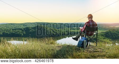 Man Hiker Sitting On Top Of The Rock, Reading Book. Beautiful Sunset Landscape. Banner.