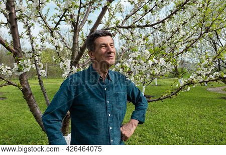 Retired But Still Good Looking Smiling Caucasian Man In Own Organic Orchard Garden. Man Is Feeling P