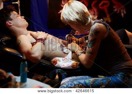 MOSCOW - MAY 20: Tattoo artist works in club ARENA-MOSCOW during V Moscow International Tattoo Convention 2012, May 20, 2012, Moscow, Russia. Convention was organized by Tattoo Studio Angel.