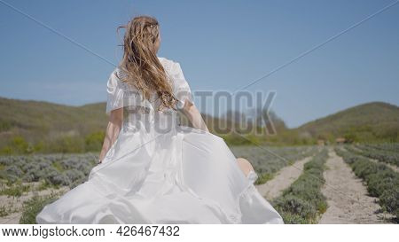 Beautiful Young Woman In White Dress Runs Across Field. Action. Womans Hair And Dress Flutter Beauti