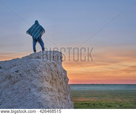 Man in a Mexican poncho watching sunrise over prairie - summer scenery in Pawnee National Grassland in northern Colorado