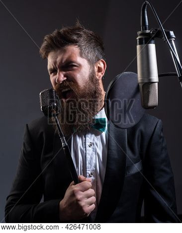 Portrait Of Bearded Man With Microphone Singing Song. Musician In Music Hall. Funny Guy Singing In K
