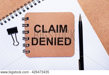 On A Wooden Background Notepad, Black Pen, Paper Clip And Brown Notepad With The Text Claim Denied.