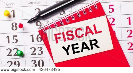 On The Calendar Is A White Card With The Text Fiscal Year. Nearby Is A Red Notepad And A Marker. Vie