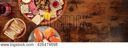 Gourmet Wine Snacks Panorama. A Glass Of Red Wine And A Platter With Olives, Blue Cheese And Other C