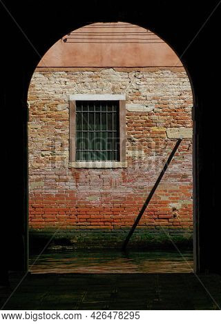 Dark Interior Opens Through Archway To Ancient Red Brick Wall And Window With Bars. Beautiful Green