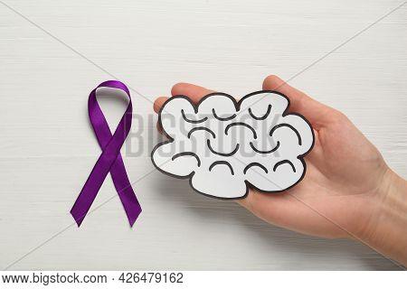 Woman Holding Paper Brain Cutout Near Purple Ribbon On White Wooden Background, Top View. Epilepsy A