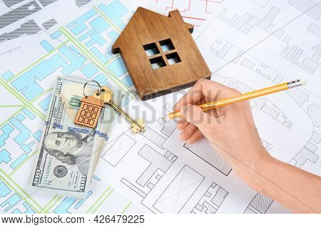 Cartographer With Key, House Model And Money Drawing Cadastral Map, Closeup