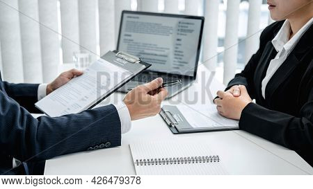 Man Employer In Suit Is Holding Resume Of Applicant To Reading Her Profile And Asking Candidate Ques