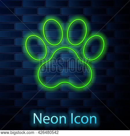 Glowing Neon Line Paw Print Icon Isolated On Brick Wall Background. Dog Or Cat Paw Print. Animal Tra