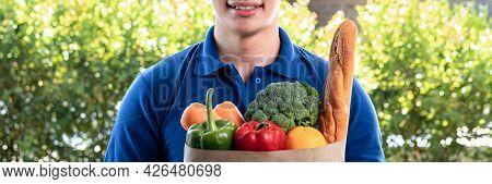 Asian Delivery Man In Blue Uniform Holding Grocery Bag Of Food, Fruit, Vegetable To Sending Deliver