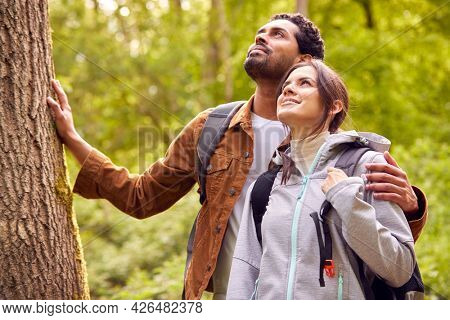 Couple Hiking Along Path Through Forest In Countryside Taking A Break And Resting Against Tree