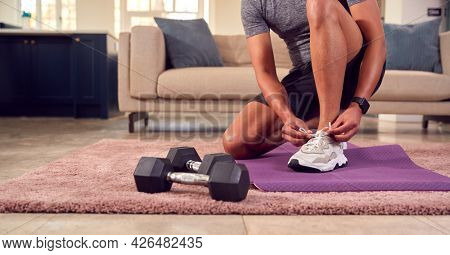 Close Up Of Man In Fitness Clothing At Home Fastening Trainers Before Exercising With Hand Weights