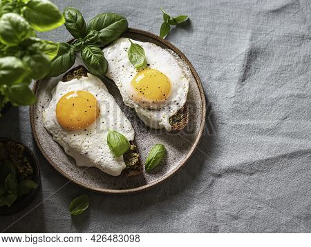 Croque-madame With Fried Egg , Pesto Sauce And Basil On A Linen Tablecloth. Traditional French Toast
