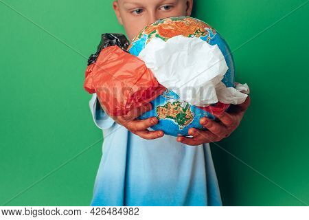 Hands Holding Planet Earth With Plastic Disposable Packages From The Middle On A Blue Background. Sa