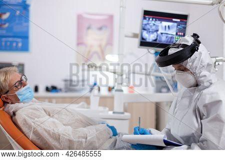 Dentist Assistant Wearing Hazmat Suit Against Coronavirus Taking Notest Talking With Senior Patient.