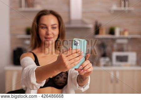 Portrait Of Beautiful Woman Looking At Phone Camera While Taking Selfie In Home Kitchen Weraring Sex